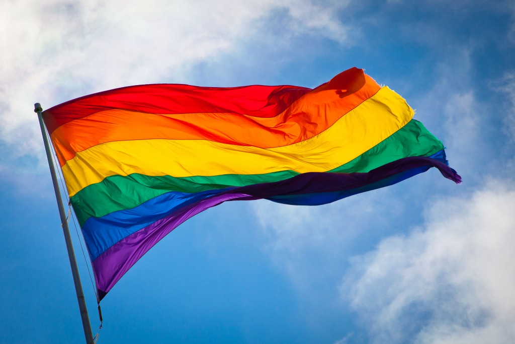 Rainbow flag blowing in the breeze against a bright blue sky with light clouds