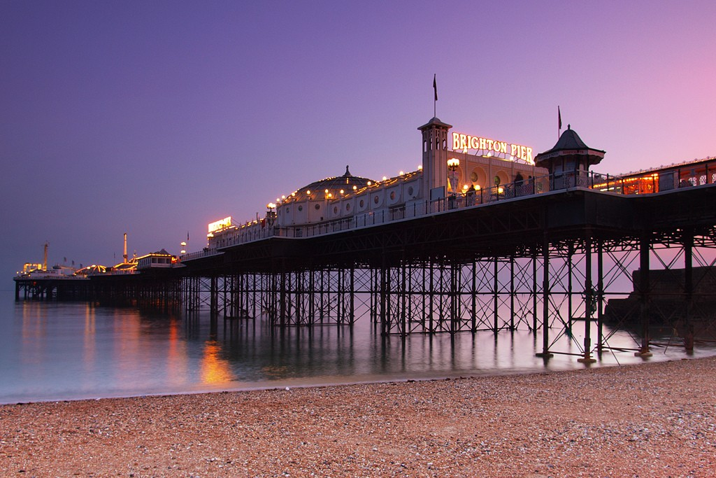 Brighton Pier shown from the beach at sunset, against a calm sea and purple sky