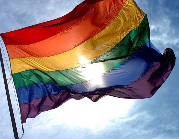 Rainbow flag with the sun behind it in a blue sky