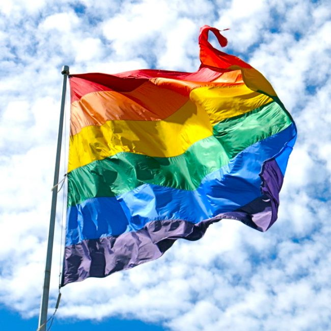 Pride Flag blowing in the wind against a blue but cloudy sky