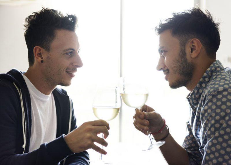 Two men on a date looking at each other whilst clinking wine glasses