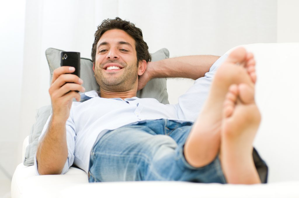 Man lying down smiling and texting
