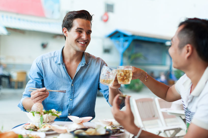 Men sitting outside a restaurant eating and smiling whilst clinking glasses